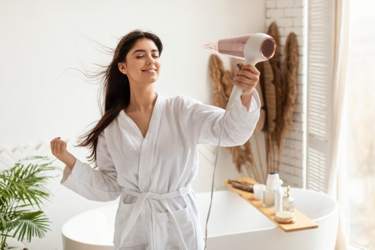 Brunette Woman Drying And Styling Hair With Hairdryer In Bathroom