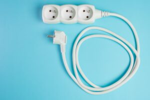 Electric extension cord on the blue background